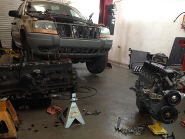 A jeep with the engine being rebuilt